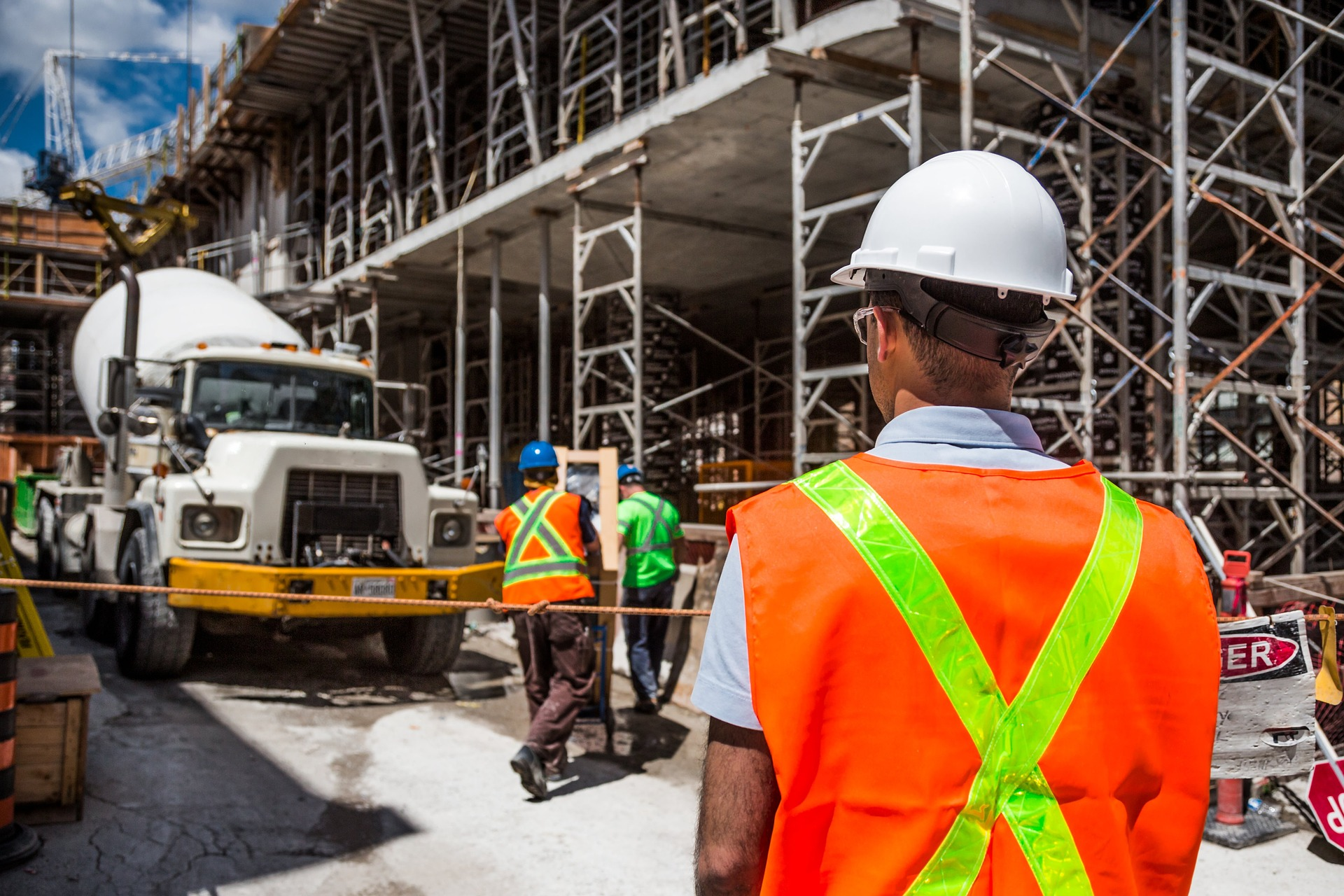 Budowa: gruszka do betonu. Robotnicy przygotowujący beton z gruszki do zalewania fundamentów.